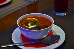 Κόκκινη πικάντικη σούπα με το λεμόνι και ελιές σε ένα άσπρο πιάτο στοκ εικόνες
