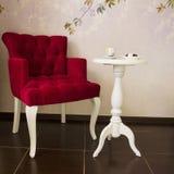 Κόκκινη πολυθρόνα και άσπρη στρογγυλή θέση τραπεζάκι σαλονιού που χαλαρώνουν Στοκ Εικόνες