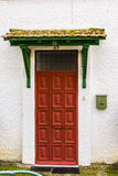 Κόκκινη πόρτα με μια στέγη Στοκ Φωτογραφία