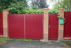 Κόκκινη πύλη μετάλλων και πόρτα και μέρος ενός φράκτη στην οδό Στοκ Εικόνες