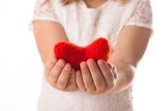Κόκκινη πλεκτή καρδιά στα χέρια των παιδιών, η έννοια Valen Στοκ Φωτογραφία
