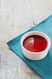 Κόκκινη σάλτσα στο λευκό σε ένα μπλε υπόβαθρο Στοκ Εικόνες