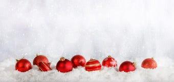 Κόκκινη σειρά σφαιρών Χριστουγέννων στο χιονώδες υπόβαθρο bokeh Χριστουγέννων Στοκ φωτογραφία με δικαίωμα ελεύθερης χρήσης