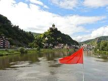 Κόκκινη σημαία και πόλη Cochem στον ποταμό Μοζέλλα Στοκ Φωτογραφία