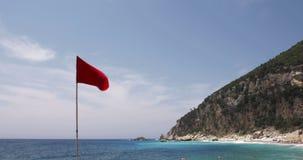 Κόκκινη σημαία προειδοποίησης στην μπλε θάλασσα, τον ουρανό και το έδαφος παραλιών στο θερινό βίντεο αέρα και θάλασσας υποβάθρου  απόθεμα βίντεο