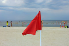 Κόκκινη σημαία σε μια αμμώδη παραλία Στοκ Εικόνες