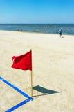 Κόκκινη σημαία στην παραλία και ένα αγόρι με μια σφαίρα Στοκ φωτογραφίες με δικαίωμα ελεύθερης χρήσης