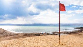 Κόκκινη σημαία στην παραλία στην κρύα ημέρα στη νεκρή θάλασσα Στοκ Εικόνα