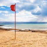 Κόκκινη σημαία στην παραλία στη νεκρή θάλασσα στη χειμερινή εποχή Στοκ Φωτογραφία