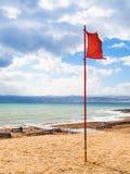 Κόκκινη σημαία στην παραλία της νεκρής θάλασσας στη θυελλώδη χειμερινή ημέρα Στοκ εικόνες με δικαίωμα ελεύθερης χρήσης