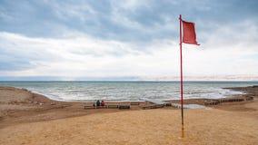 Κόκκινη σημαία στην παραλία της νεκρής θάλασσας το χειμώνα Στοκ εικόνες με δικαίωμα ελεύθερης χρήσης