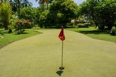 Κόκκινη σημαία στην τρύπα στον τομέα γκολφ στοκ φωτογραφία με δικαίωμα ελεύθερης χρήσης