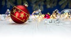 Κόκκινη σφαίρα Χριστουγέννων γυαλιού και ξύλινο παιχνίδι ελκήθρων στο πνεύμα υποβάθρου Στοκ Φωτογραφία