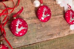Κόκκινη σφαίρα Χριστουγέννων με τα ελάφια και τις κορδέλλες στο ξύλινο υπόβαθρο invitation new year Πλαίσιο διάστημα αντιγράφων Στοκ Φωτογραφία