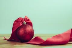 κόκκινη σφαίρα Χριστουγέννων με την κορδέλλα στην ξύλινη διαστημική πλάτη πινάκων και αντιγράφων Στοκ Εικόνες