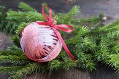 Κόκκινη σφαίρα Χριστουγέννων με τον κλάδο δέντρων έλατου στο ξύλινο υπόβαθρο Στοκ φωτογραφία με δικαίωμα ελεύθερης χρήσης