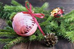 Κόκκινη σφαίρα Χριστουγέννων με τον κλάδο δέντρων έλατου στο ξύλινο υπόβαθρο Στοκ Εικόνα