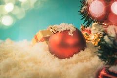 κόκκινη σφαίρα chrismas στο χιόνι με τον τρύγο υποβάθρου δέντρων chrismas Στοκ Φωτογραφία