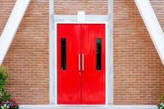 Κόκκινη σύγχρονη πόρτα με τη μακριά ανοξείδωτη λαβή στο τουβλότοιχο στο σύγχρονο κτήριο στοκ φωτογραφία