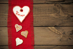 Κόκκινη σύσταση υφάσματος με τα μπισκότα καρδιών Στοκ φωτογραφίες με δικαίωμα ελεύθερης χρήσης