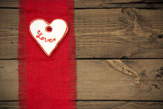 Κόκκινη σύσταση υφάσματος με το μπισκότο καρδιών Στοκ Φωτογραφίες