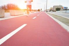 Κόκκινη τρέχοντας διαδρομή στο ηλιοβασίλεμα Τρέχοντας άτομο Στοκ φωτογραφία με δικαίωμα ελεύθερης χρήσης