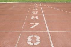 Κόκκινη τρέχοντας διαδρομή στο στάδιο στην αφετηρία Στοκ εικόνα με δικαίωμα ελεύθερης χρήσης