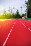 Κόκκινη τρέχοντας διαδρομή στο στάδιο, τρέχοντας διαδρομή στο μπλε ουρανό το πρωί Στοκ Φωτογραφίες
