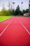 Κόκκινη τρέχοντας διαδρομή στο στάδιο, τρέχοντας διαδρομή στο μπλε ουρανό το πρωί Στοκ Εικόνες