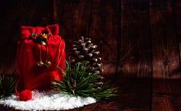 Κόκκινη τσάντα Χριστουγέννων με τον κλάδο έλατου του κώνου πεύκων στοκ φωτογραφίες