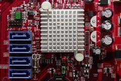 Κόκκινη τυπωμένη μητρική κάρτα υπολογιστών με το μικροκύκλωμα και τις λεπτομέρειες, κινηματογράφηση σε πρώτο πλάνο Στοκ Φωτογραφίες