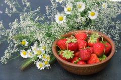 Κόκκινη φράουλα ώριμη σε ένα πιάτο αργίλου με την ανθοδέσμη τομέων μαργαριτών Gypsophila λουλουδιών σε ένα σκοτεινό υπόβαθρο Στοκ Εικόνες