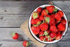 Κόκκινη φράουλα μούρων στην κούπα μετάλλων στο αγροτικό ξύλινο υπόβαθρο Άμεσα ανωτέρω Τοπ όψη Στοκ φωτογραφία με δικαίωμα ελεύθερης χρήσης