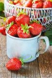 Κόκκινη φράουλα μούρων στην κούπα μετάλλων στο παλαιό αγροτικό ξύλινο υπόβαθρο από τις πρόσφατα συγκομισμένες φράουλες Στοκ φωτογραφία με δικαίωμα ελεύθερης χρήσης
