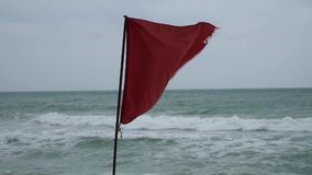 Κόκκινη ύφανση σημαιών κινδύνου στη θυελλώδη παραλία θάλασσας απόθεμα βίντεο