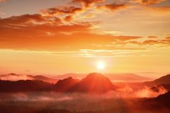 Κόκκινη misty χαραυγή Ομιχλώδες πρωί φθινοπώρου όμορφοι λόφοι Οι αιχμές των λόφων κολλούν έξω από τα πλούσια ζωηρόχρωμα σύννεφα Στοκ εικόνες με δικαίωμα ελεύθερης χρήσης