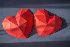 Κόκκινη polygonal μορφή καρδιών εγγράφου τρία πέρα από το ξύλινο bachground Στοκ Εικόνες