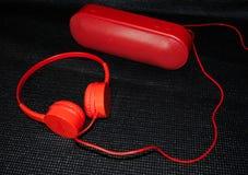 Κόκκινοι ακουστικά και ομιλητής μουσικής σε ένα μαύρο υπόβαθρο στοκ φωτογραφία