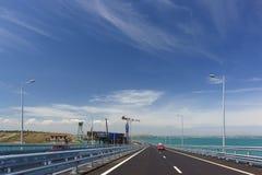 Κόκκινοι γύροι αυτοκινήτων στην της Κριμαίας γέφυρα πέρα από το στενό Kerch Στο αριστερό είναι η κατασκευή της γέφυρας σιδηροδρόμ στοκ εικόνες