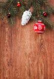 Κόκκινοι διακοσμήσεις Χριστουγέννων και κλάδος δέντρων έλατου σε ένα αγροτικό ξύλινο υπόβαθρο Στοκ εικόνα με δικαίωμα ελεύθερης χρήσης