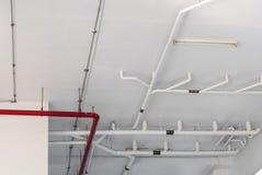 Κόκκινοι και άσπροι σωλήνες κάτω από το ανώτατο όριο στην οικοδόμηση Στοκ φωτογραφία με δικαίωμα ελεύθερης χρήσης