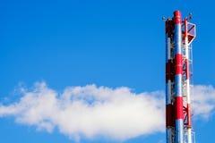 Κόκκινοι και μεταλλικοί σωλήνες εγκαταστάσεων θέρμανσης στο μπλε ουρανό υποβάθρου και το σύννεφο πίσω Στοκ εικόνα με δικαίωμα ελεύθερης χρήσης