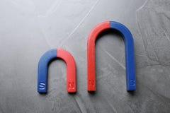 Κόκκινοι και μπλε πεταλοειδείς μαγνήτες στο γκρι στοκ φωτογραφίες με δικαίωμα ελεύθερης χρήσης