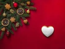 Κόκκινοι κομψοί κλάδοι υποβάθρου που διακοσμούνται με τα μελοψώματα, τους χρυσούς κώνους, τα πορτοκάλια και τις σφαίρες και ένα κ Στοκ φωτογραφία με δικαίωμα ελεύθερης χρήσης