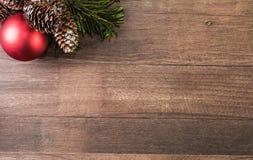 Κόκκινοι κώνοι σφαιρών και πεύκων σε ένα ξύλινο υπόβαθρο Στοκ Εικόνες