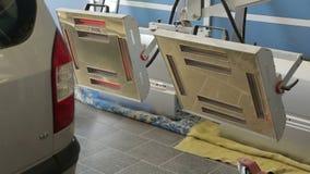 Κόκκινοι λαμπτήρες για την ξήρανση της μηχανής μετά από να χρωματίσει ή την κεραμική, γκρίζο σώμα αυτοκινήτων απόθεμα βίντεο