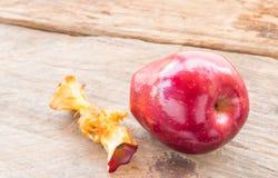 Κόκκινοι μήλο και πυρήνας μήλων σε ένα ξύλινο υπόβαθρο Στοκ εικόνα με δικαίωμα ελεύθερης χρήσης