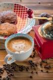 Κόκκινοι μύλος καφέ, φλυτζάνι latte με μια χρωματισμένη γάτα στον αφρό γάλακτος και μπισκότα σε έναν παλαιό ξύλινο πίνακα Στοκ Εικόνες