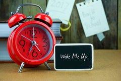 Κόκκινοι ξυπνητήρι και πίνακας στον ξύλινο πίνακα Στοκ εικόνα με δικαίωμα ελεύθερης χρήσης