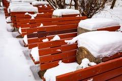 Κόκκινοι ξύλινοι πάγκοι που καλύπτονται με το χιόνι Στοκ Φωτογραφία